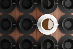 White coffee cup in the middle of a black coffee cup. Stock Images
