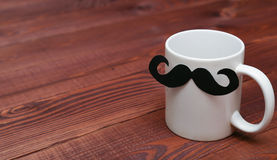 White coffee cup with mustache on wooden table. Royalty Free Stock Photos
