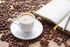 White coffee cup, notebook and pen on background of coffee beans Stock Photos