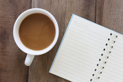 White coffee cup and notebook placed on the old wooden floor. Stock Photos