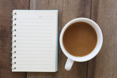 White coffee cup and notebook placed on the old wooden floor. Stock Photography