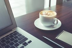 White coffee cup with notepaper and laptop on wooden desk table. /nobody.lifestyle working and drinking concepts idea Royalty Free Stock Photos