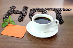 White coffee cup and paper note orange lettering t Stock Photos