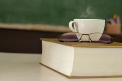 The white coffee cup is placed on the book royalty free stock photography
