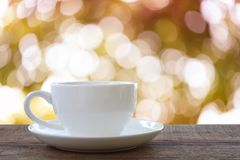 White coffee cup is placed on a brown wooden floor. White coffee cup is placed on a brown wooden floor and have a nature brown bokeh background Stock Images