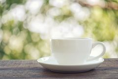White coffee cup is placed on a brown wooden floor. White coffee cup is placed on a brown wooden floor and have a nature green bokeh background Royalty Free Stock Image