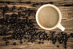 White coffee cup with roasted coffee beans on old wood. Stock Image