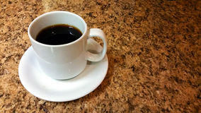 White coffee cup. And saucer on brown granite Stock Photos