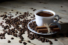 White Coffee Cup and Saucer with Cinnamon and Coffee Beans on Wooden Table Stock Photos