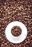 White Coffee Cup with saucer full of Roasted Coffee Beans on cof Stock Image