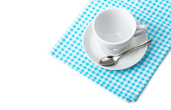 White coffee cup with saucer and spoon tableware on blue chequered napkin. On white background Stock Images