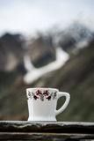 White coffee cup with snow mountain Royalty Free Stock Photography