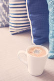 White coffee cup on sofa with pillow decoration in livingroom in Royalty Free Stock Photos