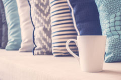 White coffee cup on sofa with pillow decoration in livingroom in Royalty Free Stock Images