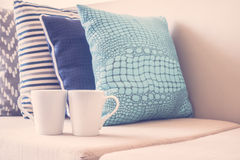White coffee cup on sofa with pillow decoration in livingroom in Stock Photography