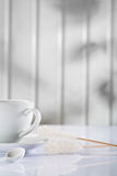 White coffee cup and spoon with sugar stick Royalty Free Stock Photo