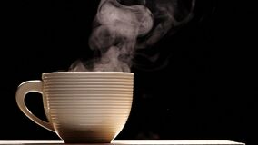White coffee cup with steam in slow motion on black background