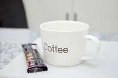 A white coffee cup on the table and on the white background Royalty Free Stock Photography