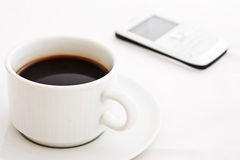White coffee cup and white mobile phone Royalty Free Stock Image