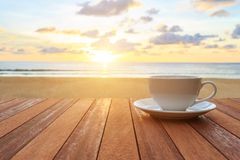 White coffee cup on wood table and view of sunset or sunrise background stock images