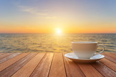 White coffee cup on wood table and view of sunset or sunrise bac. Close up white coffee cup on wood table and view of sunset or sunrise background Royalty Free Stock Photos