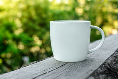 White coffee cup on wooden desk outdoors Stock Images