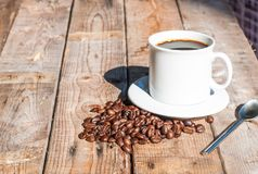 White coffee cup on wooden table background with shadow from the sunlight Royalty Free Stock Photos