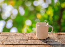 White coffee cup on wooden table at morning sunlight and bokeh b Stock Image