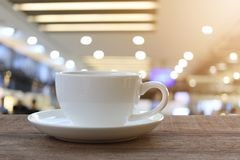 White Coffee cup on wooden table in coffee shop blur background. Royalty Free Stock Photos