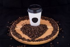 White coffee cup on a wooden tray filled with coffee beans on a. Black background stock photos