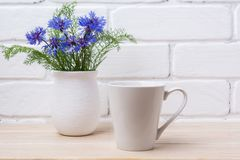 White coffee latte mug mockup with cornflower in rustic vase Stock Photo