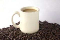 White Coffee mug. On top of beans Stock Photos
