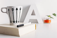 White coffee mug with arrows and diy decoration. Royalty Free Stock Images