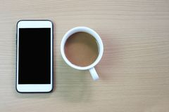 white coffee mug and blank screen of smartphone on a brown wooden floor. royalty free stock photo