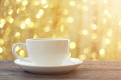 White coffee mug on brown wooden floor and have bokeh light back Stock Image