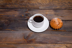 White coffee mug and cake on a wooden background Stock Image