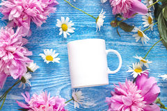 White coffee mug with chamomile flowers and pink peonies on blue Stock Photography