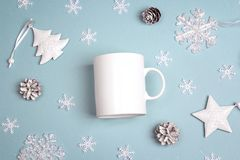 White coffee mug  with Christmas decorations on blue background. Royalty Free Stock Image