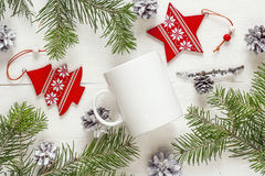 White coffee mug with Christmas decorations and fir branches. Sp Royalty Free Stock Image