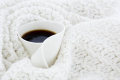 White coffee mug. Covered with white wool blanket Royalty Free Stock Image