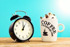 White coffee mug with cream and clock,on wooden table. Stock Photography