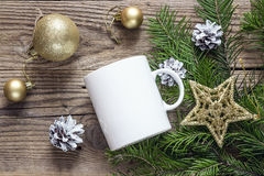 White coffee mug with gold Christmas decorations and fir branche Stock Photo