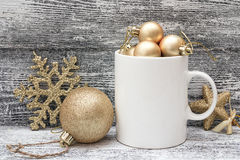 White coffee mug with gold shiny Christmas decorations. Space fo Stock Photo