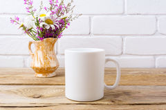 White coffee mug mockup with chamomile and purple flowers in gol Stock Photo