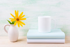 White coffee mug mockup with golden yellow rosinweed in pitcher Stock Photo