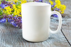 White coffee mug mockup with lilac and yellow flowers Stock Photography