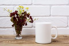 White coffee mug mockup with maroon and yellow grass Stock Photos