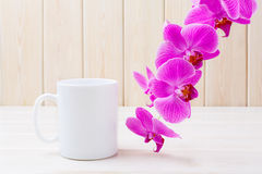 White coffee mug mockup with pink orchid Royalty Free Stock Photo