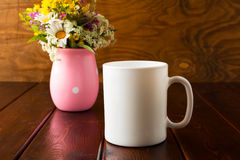 White coffee mug mockup with wild flowers Royalty Free Stock Images