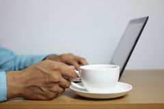 White coffee mug placed on a brown wooden table and a man working on laptop. stock images